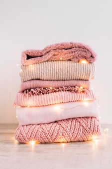 Stack of knitted sweaters with garland on floor