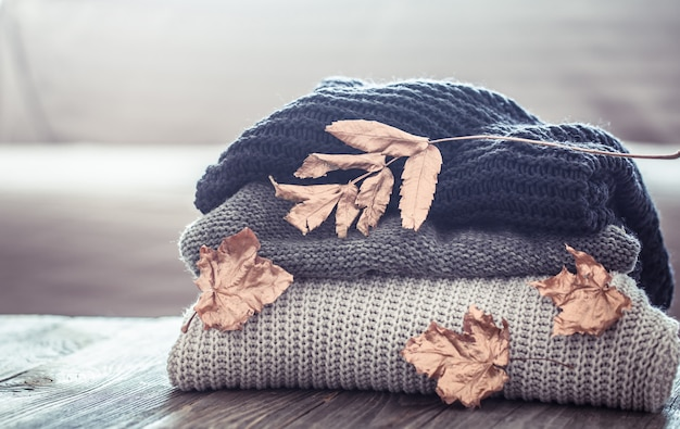 Stack of knitted sweaters on a wooden table