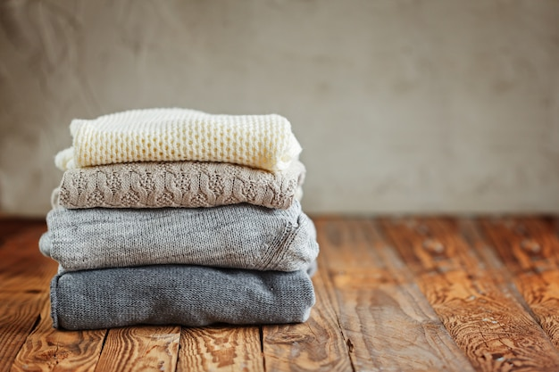 Stack of knitted winter clothes on wooden, sweaters
