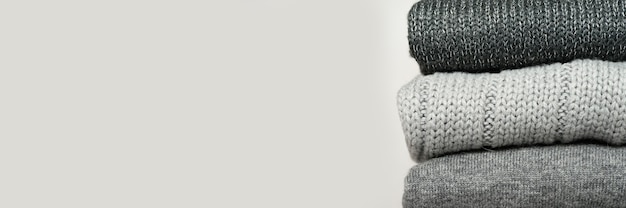 A stack of knitted winter sweaters in several shades of gray on gray background. banner