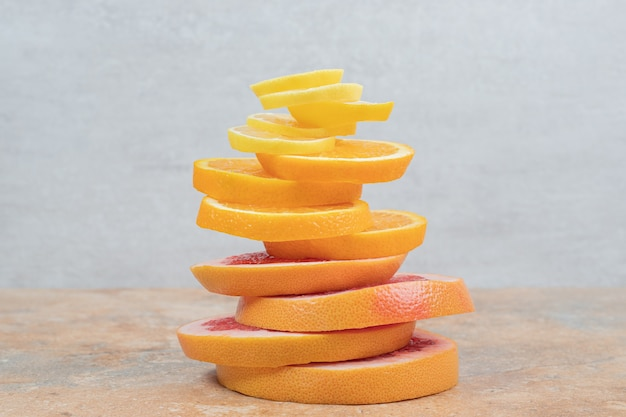 Stack of lemon, orange and grapefruit slices on marble table. high quality photo