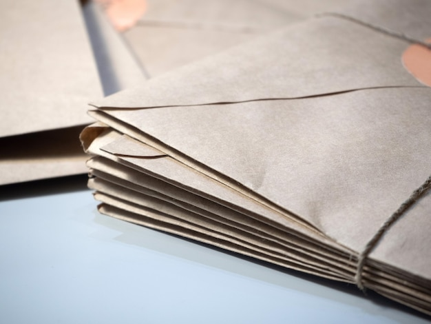 A stack of letters in kraft envelopes lies on the table tied with string