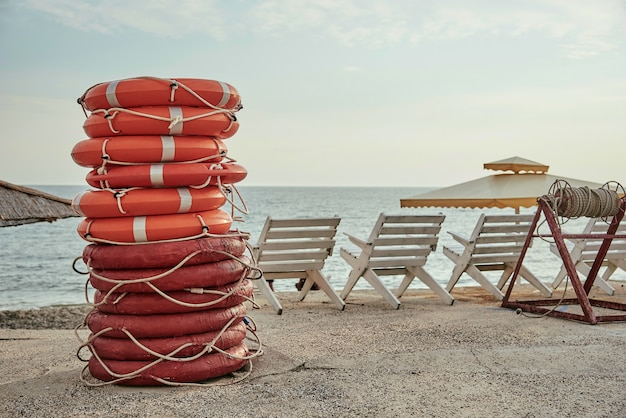A stack of lifebuoys on the beach.