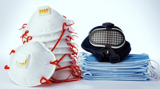Stack of medical masks with respirator on white background