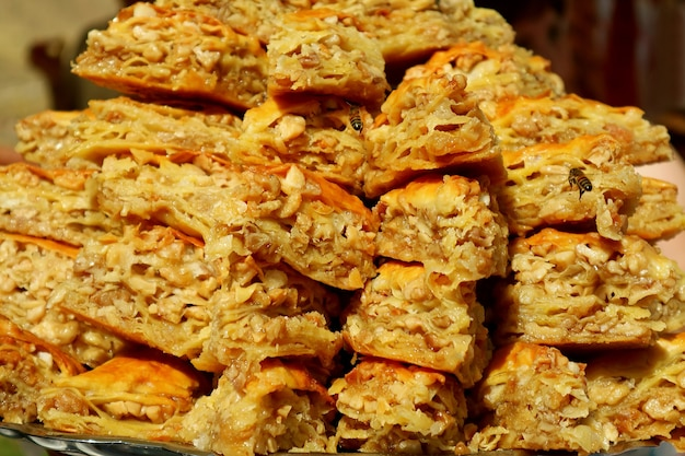 Stack of mouthwatering baklava pastries attracting hungry bees at the local market of armenia