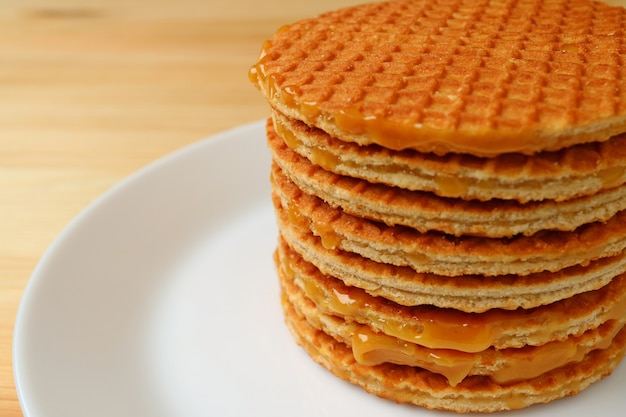 Stack of mouthwatering stroopwafels on the white plate served on wooden table