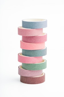 Stack of multi-colored rolls of washi tape on a white