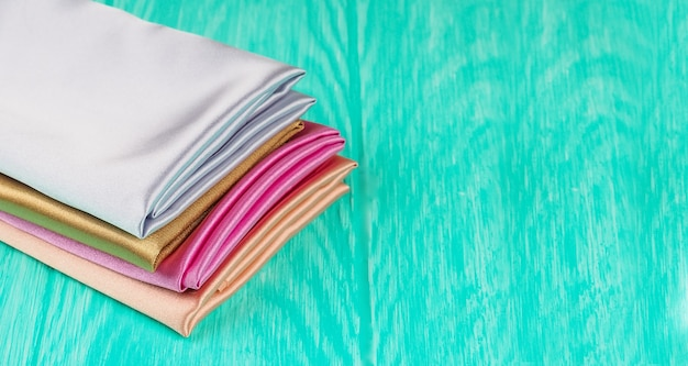 A stack of multi-colored satin fabric on a blue background, space for text.