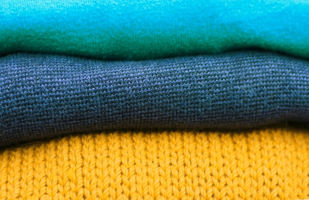 Stack of multicolored and trend ceylon yellow woolen knitted sweaters close-up, texture, background