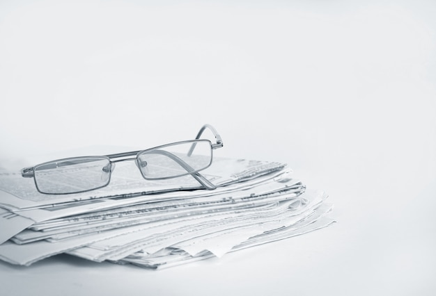 Stack of newspapers and glasses isolated on white
