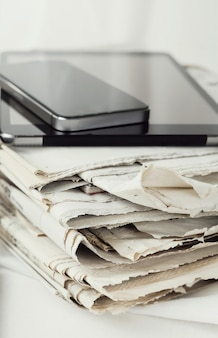 Stack of newspapers with digital tablet and smartphone
