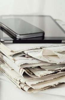 Pila di giornali con tavoletta digitale e smartphone