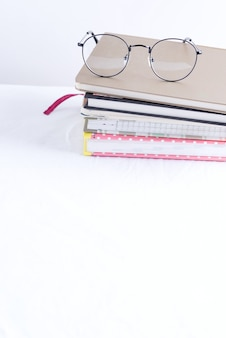 Stack of note books for notes and annotations with glasses on the top on a white table.
