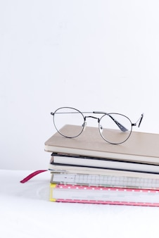 Stack of note books for notes and annotations with glasses on the top on a white table