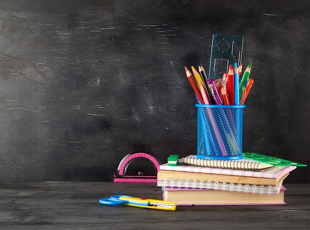 Stack of notebooks, blue glass with multi-colored wooden pencils and pen