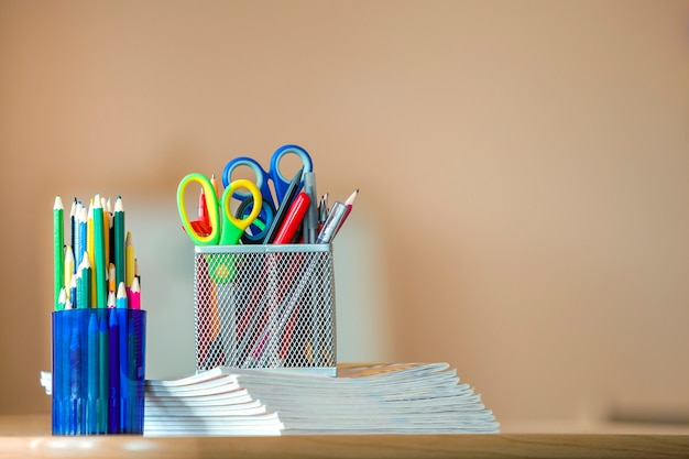 Stack of notebooks, colorful drawing pencils and stationery arrangement on copy space .