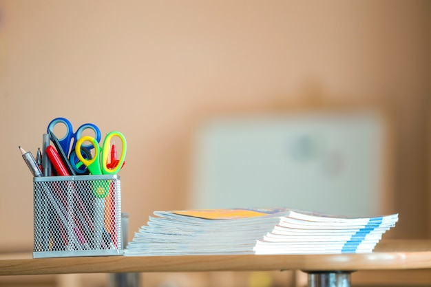 Stack of notebooks and stationery arrangement in classroom or office on copy space background