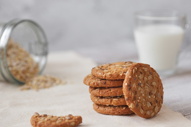 A stack of oatmeal cookies, a glass of milk, cereal on a wooden table and a gray