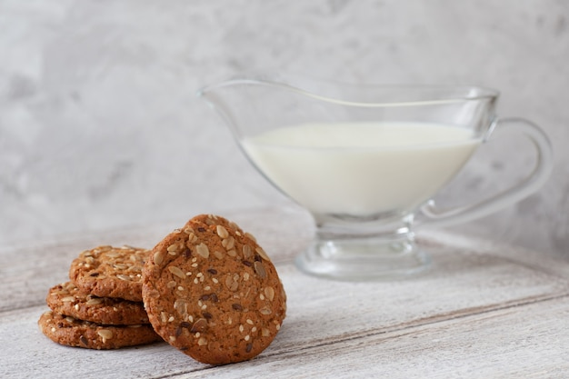 A stack of oatmeal cookies, a jug of milk, cereal on a wooden table and a gray