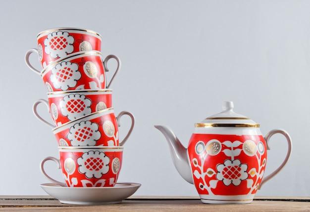 Стек старинных керамических чашек и чайник на деревянный стол на белой стене