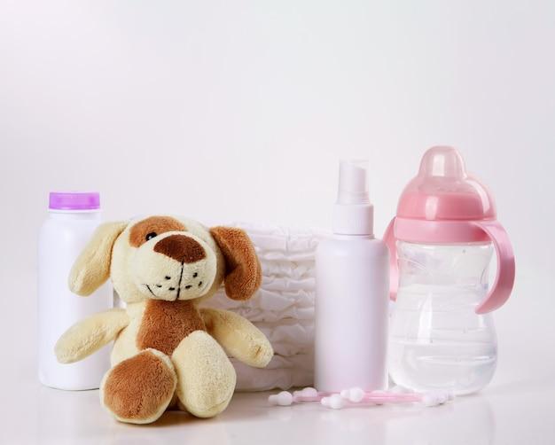 白い背景の上の赤ちゃんの使い捨ておむつ、ぬいぐるみ、香りのボトルと哺乳瓶のスタック