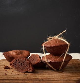焼きたてのブラウニーラウンドケーキのスタックは茶色の木の板にロープで縛ら