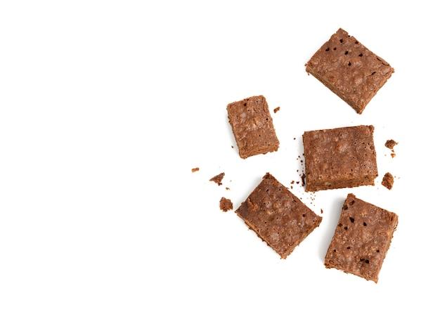 Стек запеченных кусочков шоколадного брауни с грецким орехом, изолированные на белом фоне, вкусный десерт, копией пространства