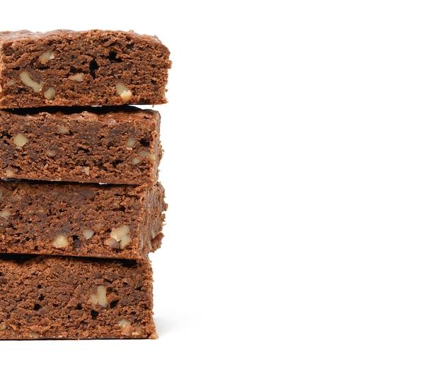 Стопка запеченных кусочков шоколадного брауни с грецким орехом, изолированные