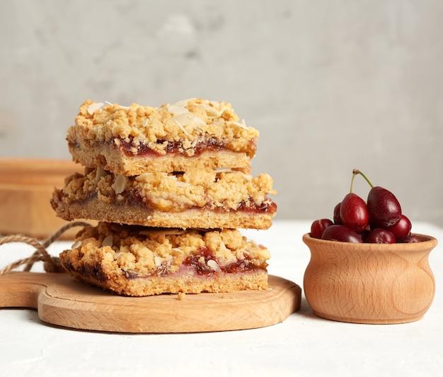 Стопка запеченного крошечного пирога с фруктовой начинкой, посыпанного тертым миндалем на деревянной доске