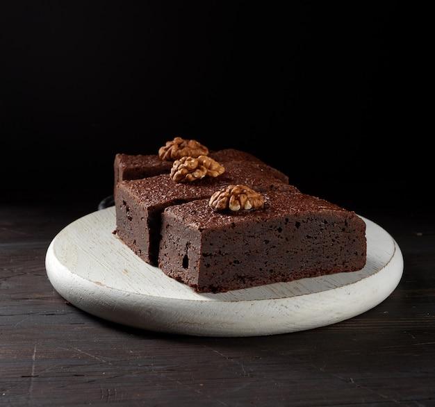 Стек запеченных кусочков шоколадного торта брауни с орехами на деревянной доске, вкусный десерт, крупным планом