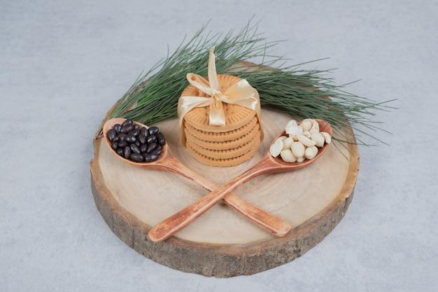 木の板にリボン、ピーナッツ、チョコレートのかけらで結ばれたビスケットのスタック。高品質の写真
