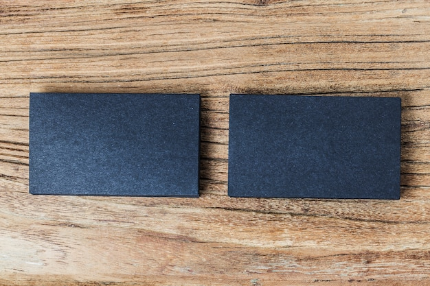 Стек пустых черных визитных карточек на деревянном фоне