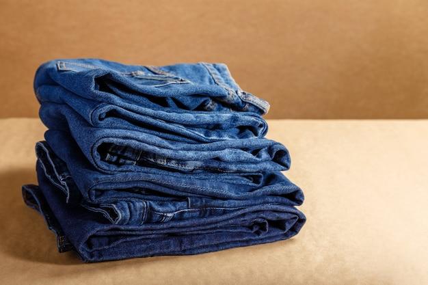 블루 데님 옷의 스택입니다. 복사 공간이 있는 갈색 공예 배경에 파란색의 다른 음영으로 접힌 파란색 데님 바지를 쌓습니다.