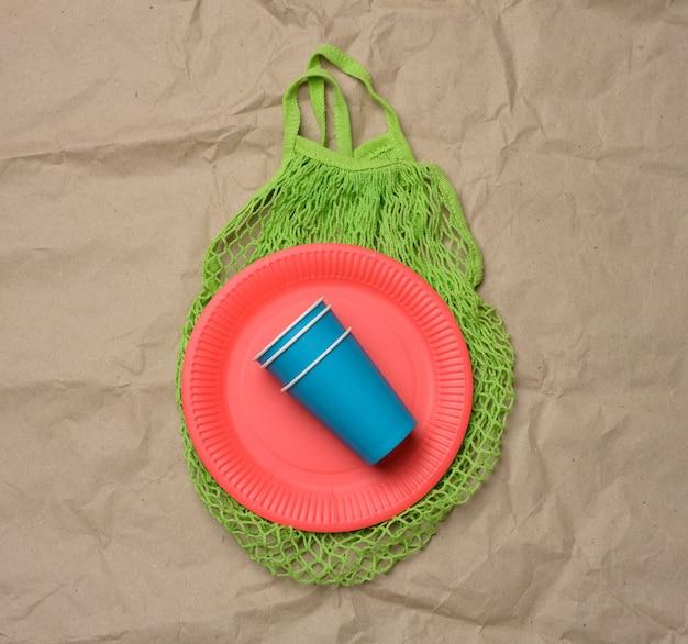 Стек синих бумажных стаканчиков и красных круглых тарелок на коричневом бумажном фоне. концепция отбраковки пластика, нулевые отходы