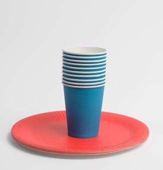 白い背景の上の青い紙コップと赤い丸いプレートのスタック。プラスチック拒否の概念、ゼロウェイスト