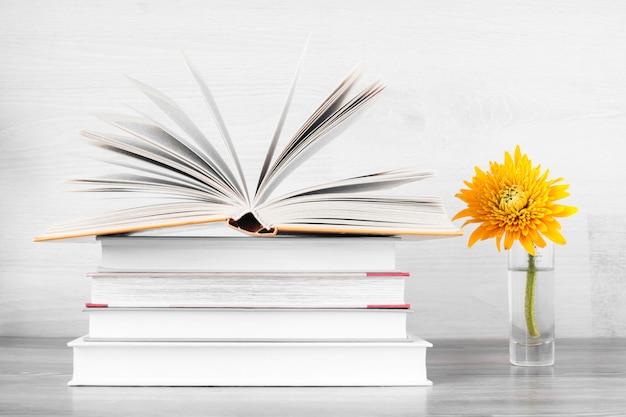 Стопка книг и желтый цветок в вазе.