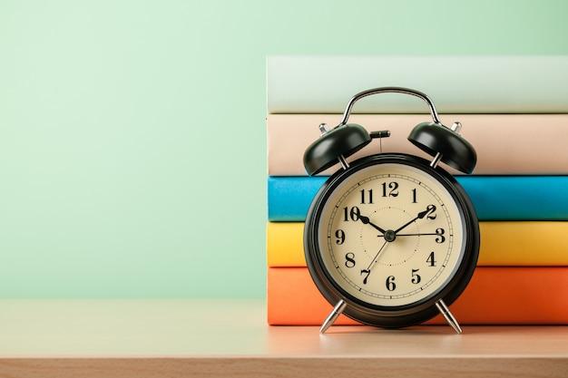 Стопка книг и будильник на деревянном столе