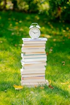 가을에 푸른 잔디에 책과 알람 시계의 스택