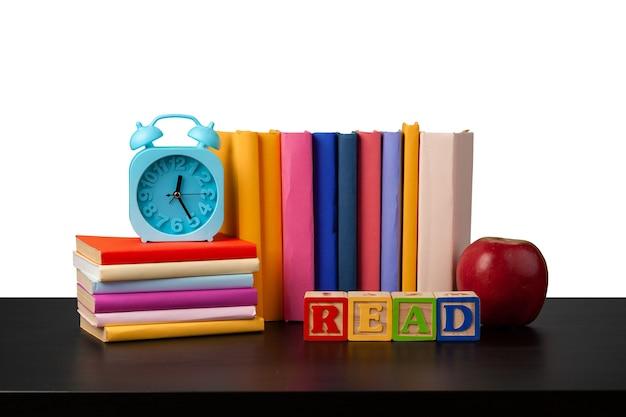 白い背景の上の卓上に本とリンゴのスタック