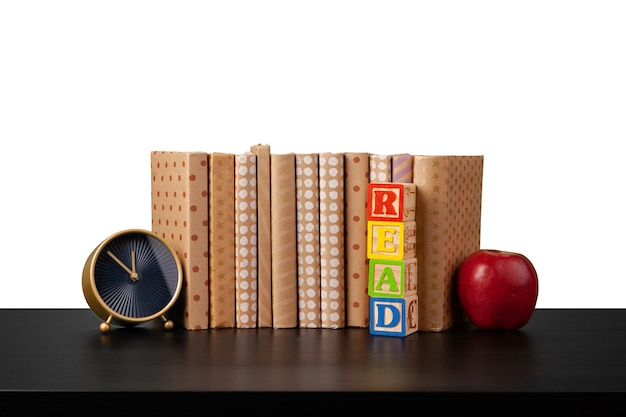 Стопка книг и яблоко на столе на белом фоне
