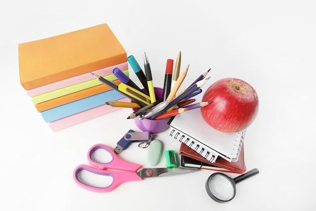 Стопка книг и красочные школьные принадлежности на белом фоне