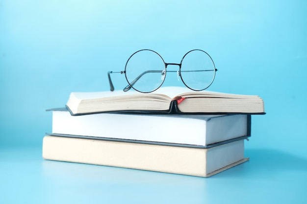Стек книг и очков на синем фоне
