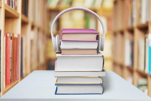 나무 테이블에 책과 헤드폰의 스택