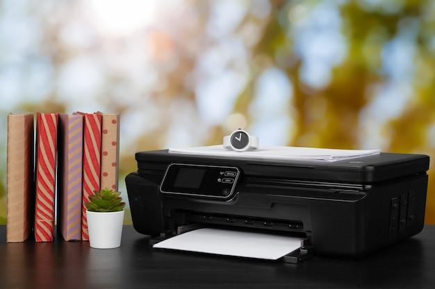 흐릿한 배경에 대해 책과 가정용 프린터 더미를 닫습니다.