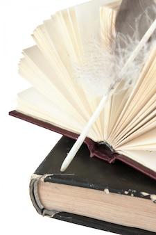 Стопка книг и перо на белом фоне