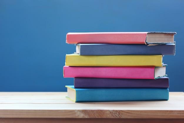 Стопка книг в цветной обложке на столе.