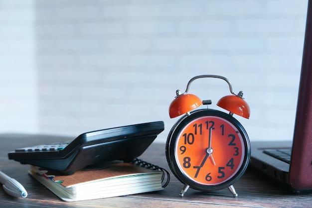 本、ラップトップ、テーブルの上の時計のスタックをクローズアップ。