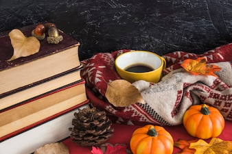 Stack of books near drink and autumn symbols