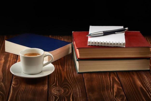 Стопка книг, блокнот, чашка кофе эспрессо и ручка на темноте.
