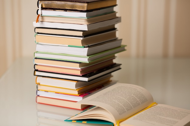 自宅の机の上の本のスタック。ベージュの縞模様の背景。空きスペース